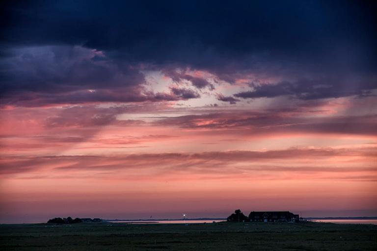 links die Warften Süderhörn und Mayenswarf, rechts Norderhörn, mittig der Leuchtturm der Insel Amrum